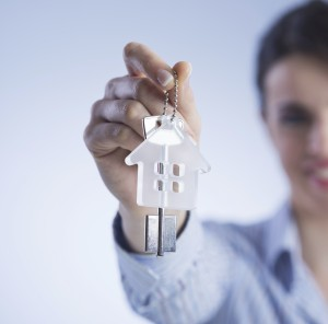 a woman holding up a key for renting a house